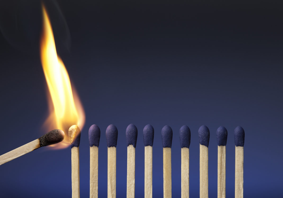 A photograph of blue-tipped matches on a blue background.  A single lit match is coming in from the left side of the image and beginning to ignite the leftmost match.  The tip of the lit match is black, and the flame is orange.  The background of the picture is deep blue at the top and gradually lightens to a brighter blue as it reaches the bottom of the image.